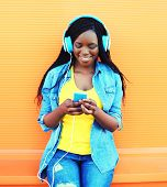 Fashion Pretty Smiling African Woman With Headphones Listens To Music Over Orange Background poster