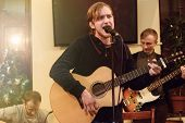 Постер, плакат: Stylish Vocalist With Beard Performing Lyrical Song On Stage With His Band