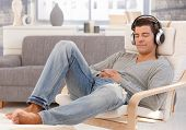 Handsome guy enjoying music on headphones, sitting in armchair with eyes closed, smiling.?