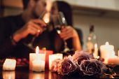 Beautiful passionate couple having a romantic candlelight dinner at home, drinking wine, toasting poster