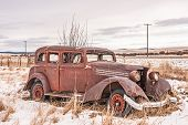 Rusty, Dilapidated, Abandoned Vehicle In A Field In Rural America.  There Is Some Snow In The Field  poster