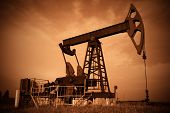 stock photo of nonrenewable  - Oil pump jack dark Red filtered image - JPG