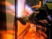 Welder Worker Performs Jump Welding. Worker Welder Performs Arc-welding Process Of Metal Structures. poster