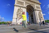 Woman With Yellow Vest Jumping At Arch Of Triumph. Popular Landmark In Paris, France. Concept Of Hap poster
