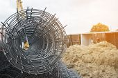 Rolls Of Wire Mesh Steel For Construction Put A Pile On The Ground, Against Construction Site Backgr poster