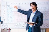 Young male chemistry teacher in front of periodic table  poster