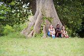 Three Happy Female Friends Sitting Near Big Tree