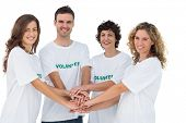 Smiling volunteer group piling up their hands on white background