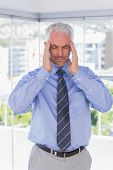 Stressed businessman rubbing his temples with eyes closed standing in his office