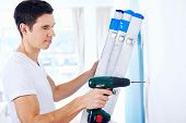 man doing diy drilling in new home after moving in standing on ladder