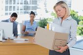 Sad businesswoman leaving office after being let go holding box of belongings