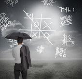 Businessman looking at noughts and crosses and holding umbrella