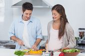 Man chopping mushrooms next to his pregnant partner in the kitchen