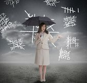 Businesswoman with noughts and crosses holding umbrella and smiling