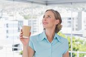 Happy businesswoman holding disposable coffee cup and looking up in bright office