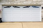 stock photo of garage  - double white wooden garage door with partial driveway - JPG