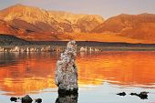 Orange sunset. The magic of Mono Lake. Outliers - calcareous tufa formation  on the smooth water of