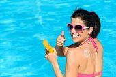 Mulher feliz aplicando filtro solar no verão