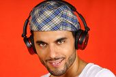 stock photo of beret  - Smiling 30 years old man with beret and earphones over an orange background