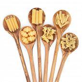 Pasta selection of penne, gnocci, rigatoni, casarecce, fiorelli and algar in wooden spoons over white background.
