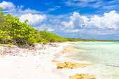 Deserted tropical beach at Cayo Coco (Coco key) in Cuba on a beautiful day with puffy white clouds o