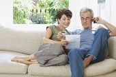 Middle aged couple paying bill by phone on couch at home
