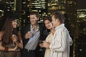 Dos parejas de jóvenes bebiendo juntos contra el horizonte de la ciudad por la noche