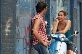 Cheerful young woman on moped talking to man against wall