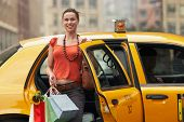 Portrait of a smiling young woman with shopping bags exiting yellow taxi