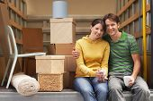 foto of moving van  - Portrait of smiling young couple sitting back of moving van - JPG