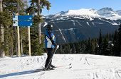 Skier Stopped On Ski Trail, Looking At Slopes