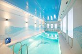 Indoor pool with images of dolphins at bottom and clear water in big room.