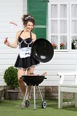 Beautiful housemaid keeps lid and sausage on fork near barbecue near country house.