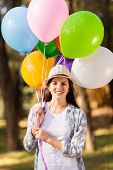 beautiful teenage girl holding bunch of helium balloons outdoors
