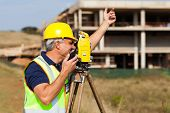 senior land surveyor talking on walkie talkie at construction site