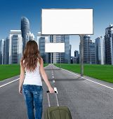 woman walking on the road to the city, in front of an empty Billboards. concept. tourist returns hom