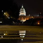 Capitol Building and reflection over rain pools at night - Washington DC