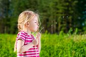 Pretty Blonde Little Girl With Closed Eyes Blowing A Dandelion And Making Wish