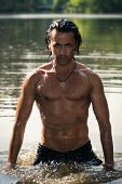 stock photo of half naked  - Young man with half naked standing in the river - JPG