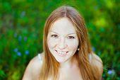 Schöne Rothaarige lächelnde junge Frau sitzt auf dem Rasen