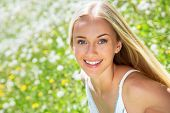 stock photo of blow-up  - Beautiful young woman in a clearing among the flowers - JPG
