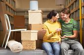 stock photo of moving van  - Smiling young couple holding home key while sitting back of moving van - JPG