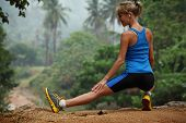 Young slim lady stretching before running in a forest
