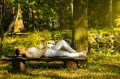 Woman With Eyes Closed Relaxing On A Bench In Nature