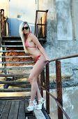 The beautiful woman the blonde in bikini background an old ladder