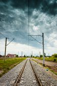 Straight Railroad With Dark Cloudy Sky