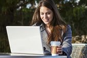 stock photo of takeaway  - A young woman or girl student using a laptop outside and drinking takeaway coffee - JPG