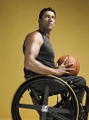 Side view of a confident paraplegic athlete in wheelchair holding basketball against yellow backgrou