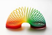 picture of coiled  - Rainbow coloured slinky toy made of a plastic wire spiral coil which enables flexibility and mobility - JPG
