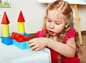 Child preschooler play wood block in play room. Child care.